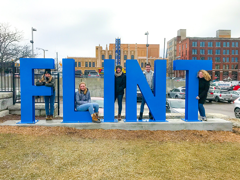 students standing behind flint sign in grass
