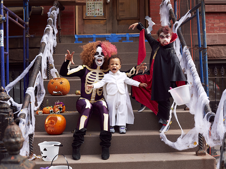 woman with halloween makeup stands with boy in white outfit on stoop in halloween costumes