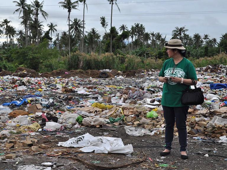 Susan Gallardo looking at pile of garbage