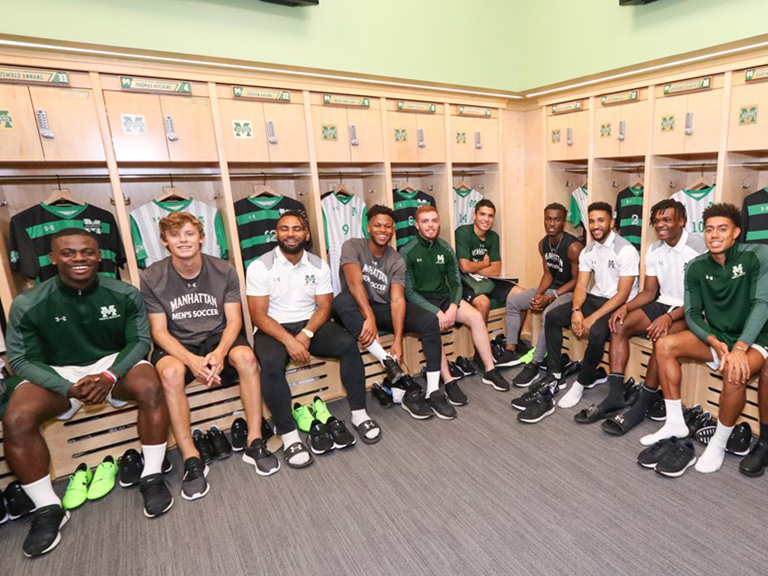 Men's soccer players sitting at lockers in Gaelic Park Athletic Center