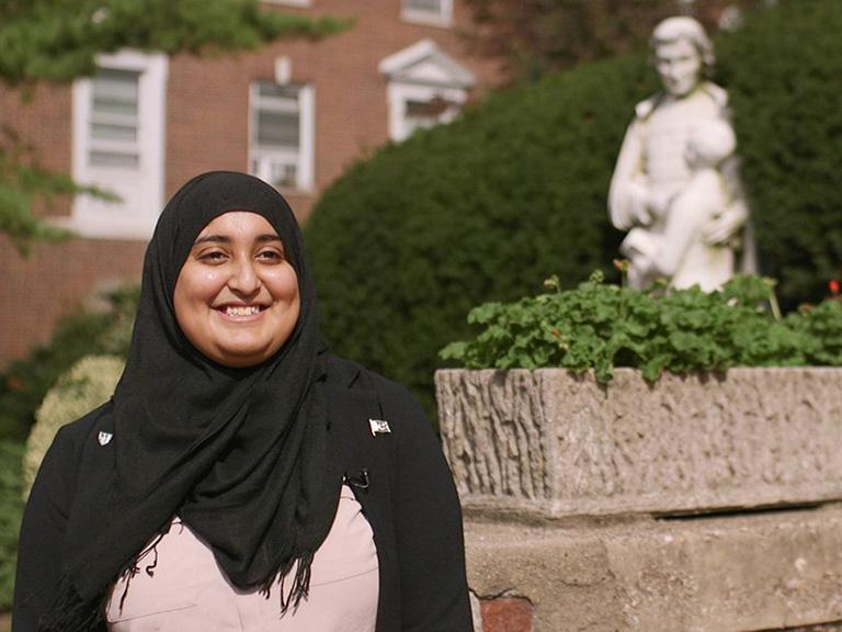 Rabea Ali in front of John Baptist de La Salle statue