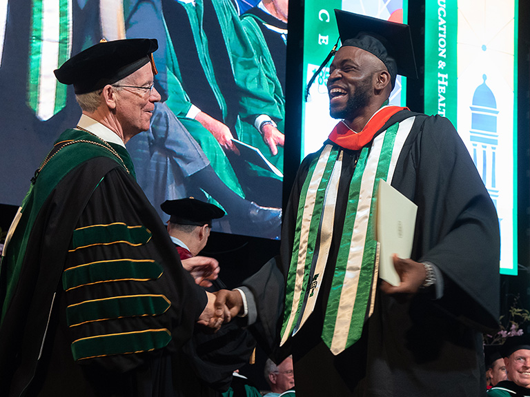 Samson Usilo walking across stage at graduation