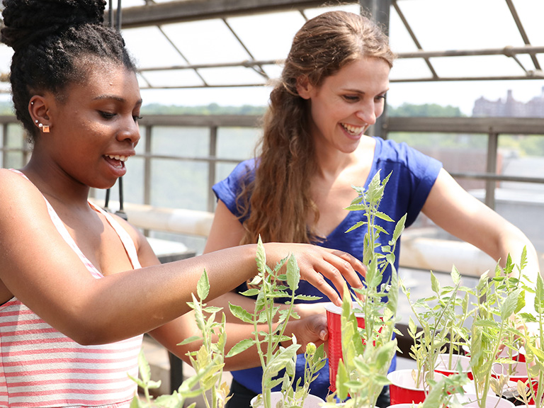 Sarah Wacker and student working on biofilm project on rooftop garden