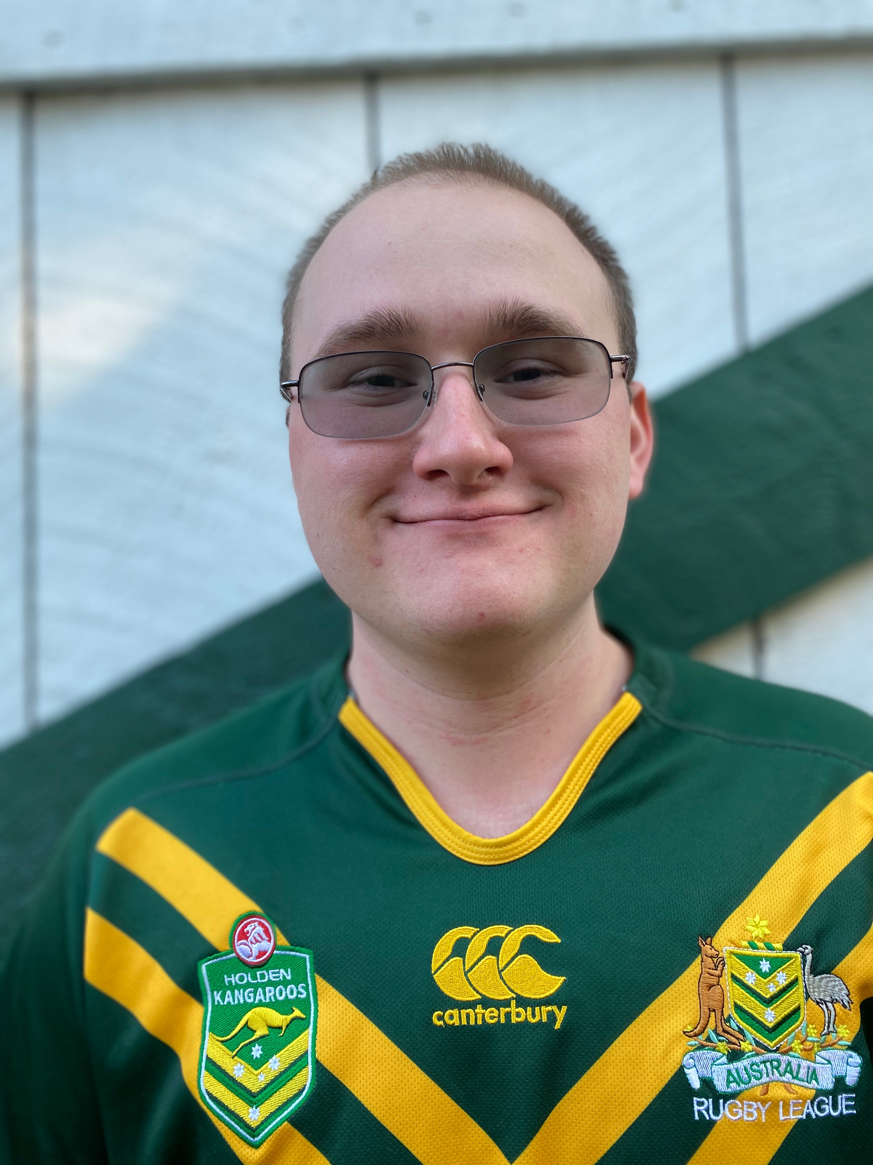 Matthew Sweeney smiling and wearing a green jersey.