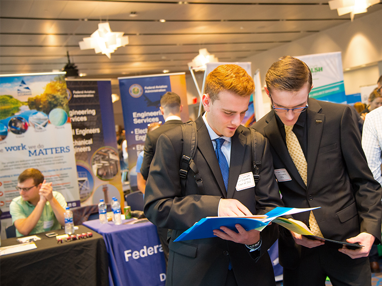 Two students dressed for success analyzing a folder of employers at the Manhattan College STEM Career fair in Kelly Commons.