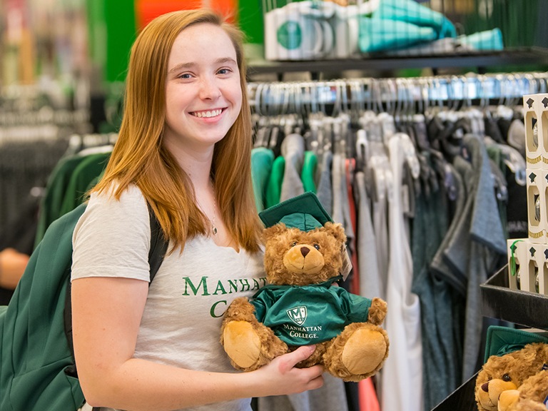 Ellen Farrelly smiling in Manhattan College's bookstore holding a teddy bear dressed in a graduation gown.