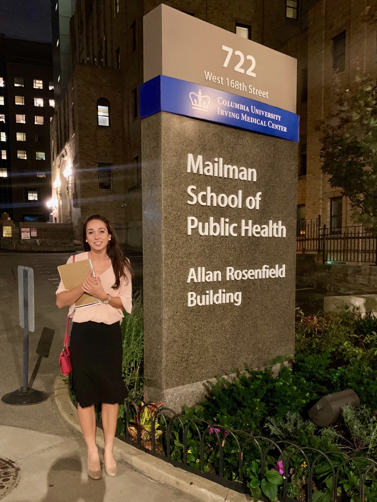 "Emma Kaishian standing in front of Columbia University's Iriving Medical School sign that reads ""Mailman School of Public Health""."