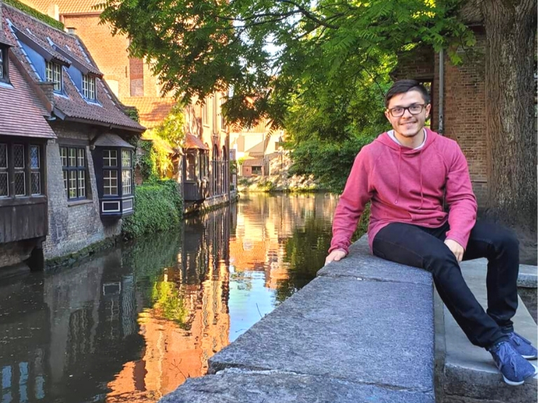 Miguel Diaz-Lopez sitting next to a river in europe.