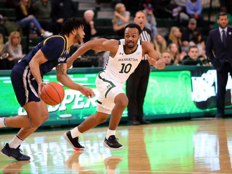 manhattan basketball player dribbles ball during game on campus