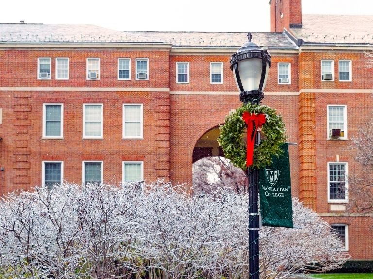 green holiday wreath with red bow in front of brick building