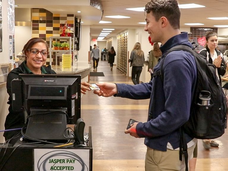 male student hands manhattan college id card to dining worker