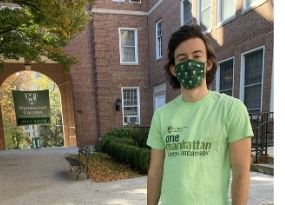 young man with dark hair and green t shirt during a sunny day on the campus quadrangle