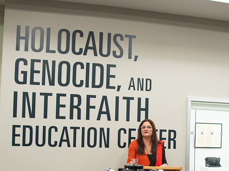 Mehnaz Afridi standing in front of HGI Center banner