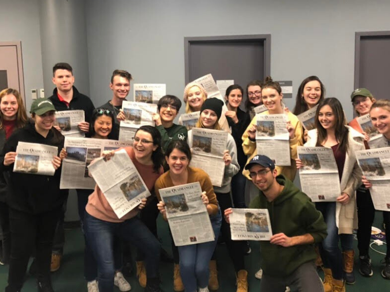 members of student newspaper the quad holding up newspapers