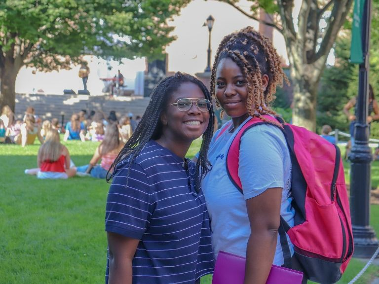 two young women standing on manhattan college quad during campus social event