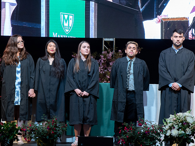 college seniors being recognized on stage at ceremony
