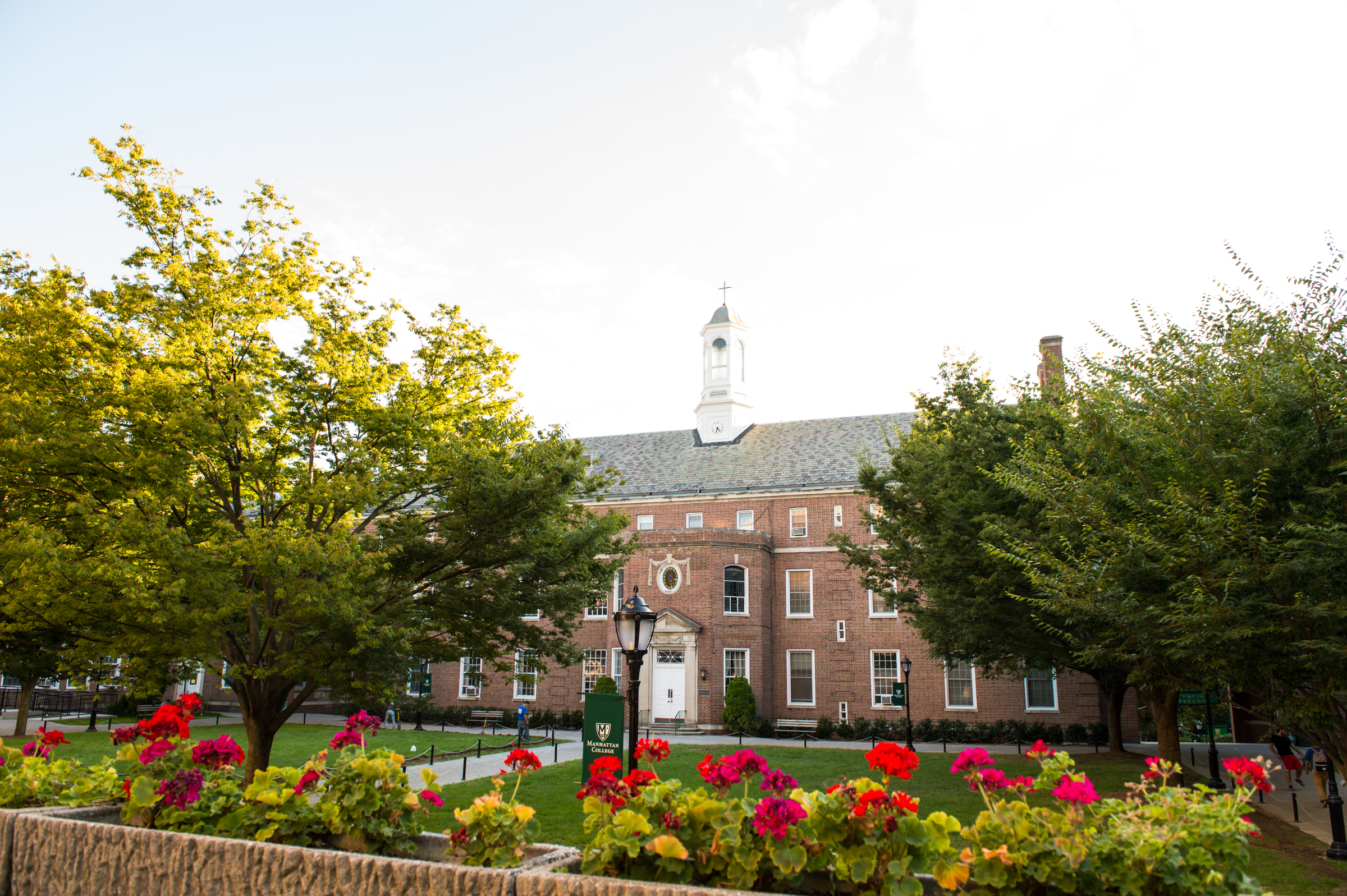 Manhattan College's quad with trees and flowers in bloom.
