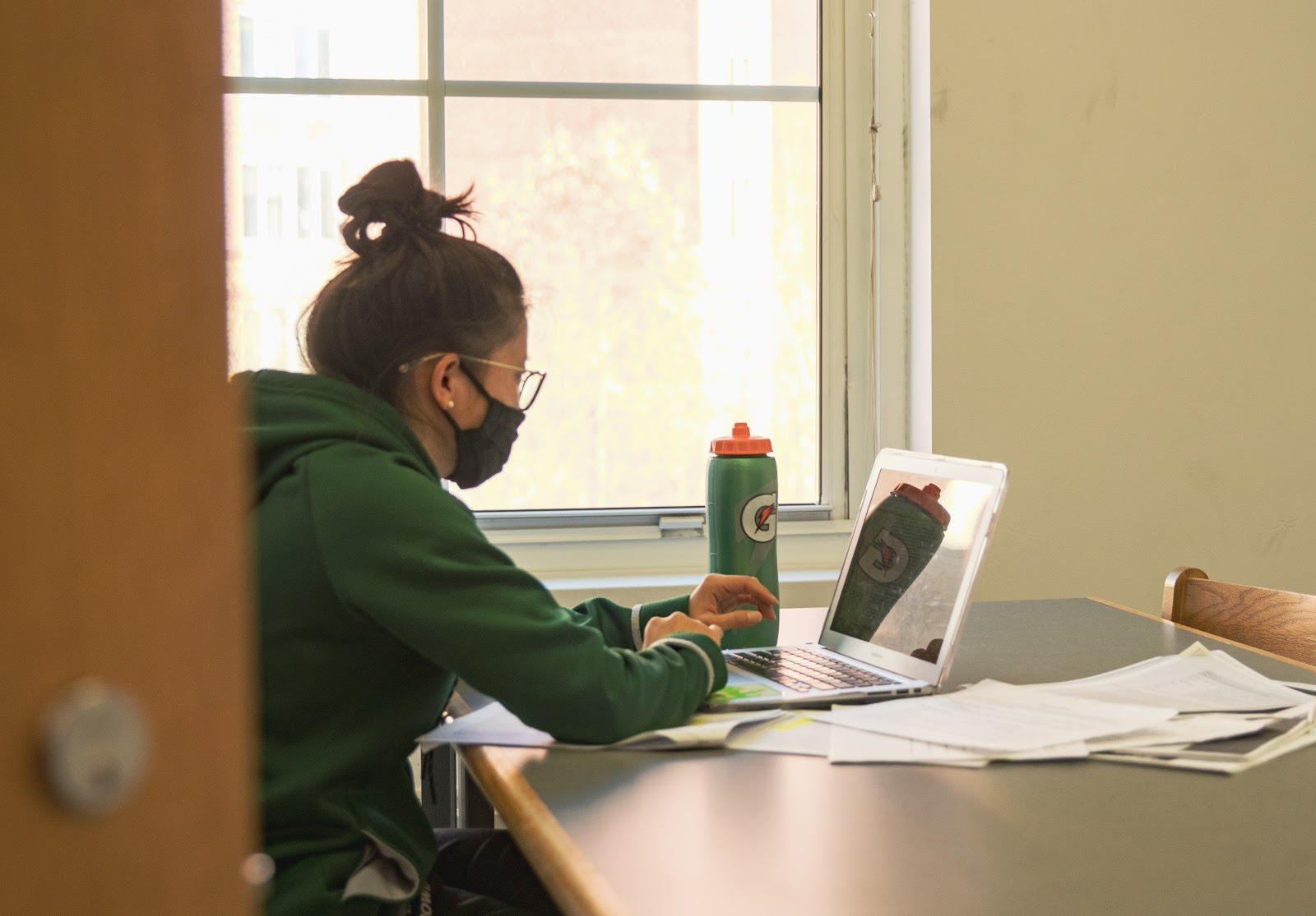 Student sitting down with mask using laptop in a library
