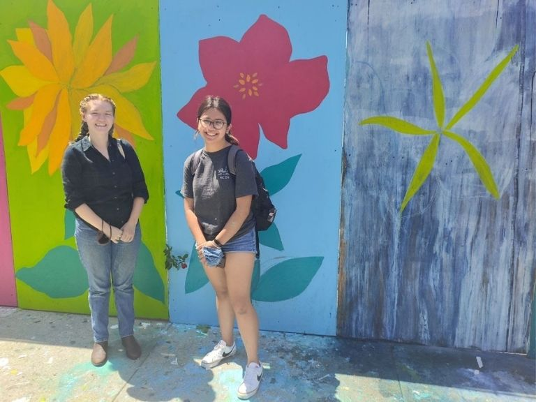 two young women standing in front of mural on sunny day