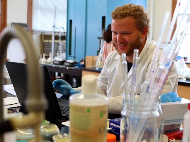 man with blond hair performing experiment in science lab