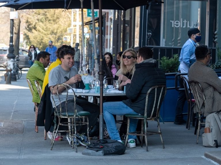 men and women eating at restaurant outdoors in new york city
