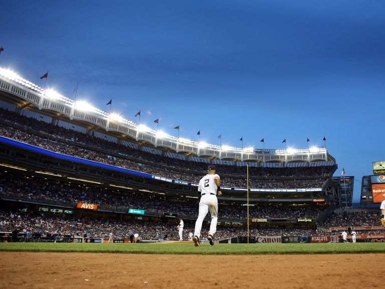 baseball player jogging on field in crowded stadium
