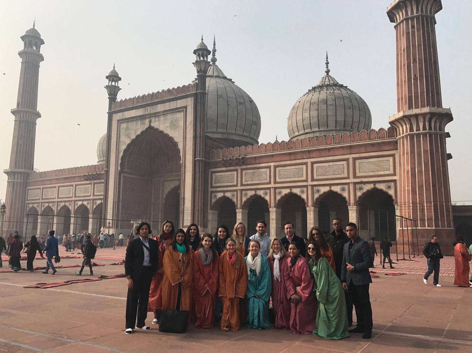 business cohort stands in front of indian mosque