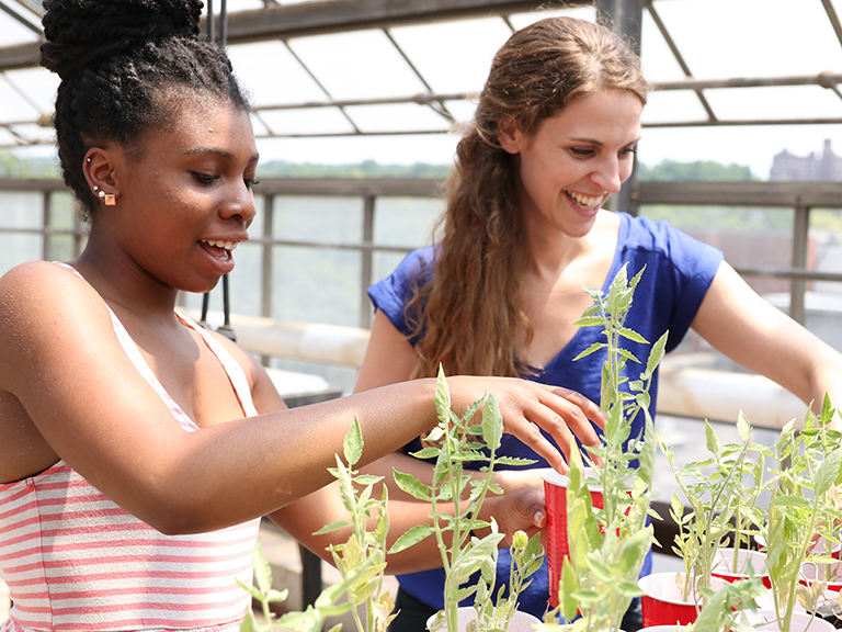 An image of female professor and student looking at plants in greenhouse