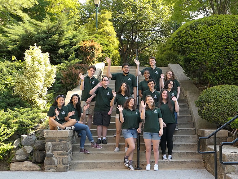 orientation leaders smile on steps of campus.