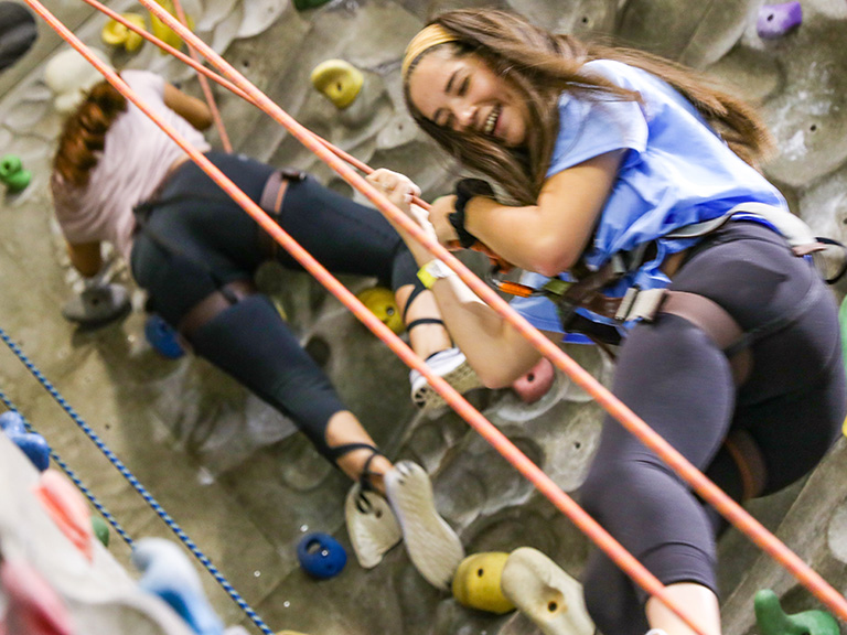 female student smiling on indoor rock wall