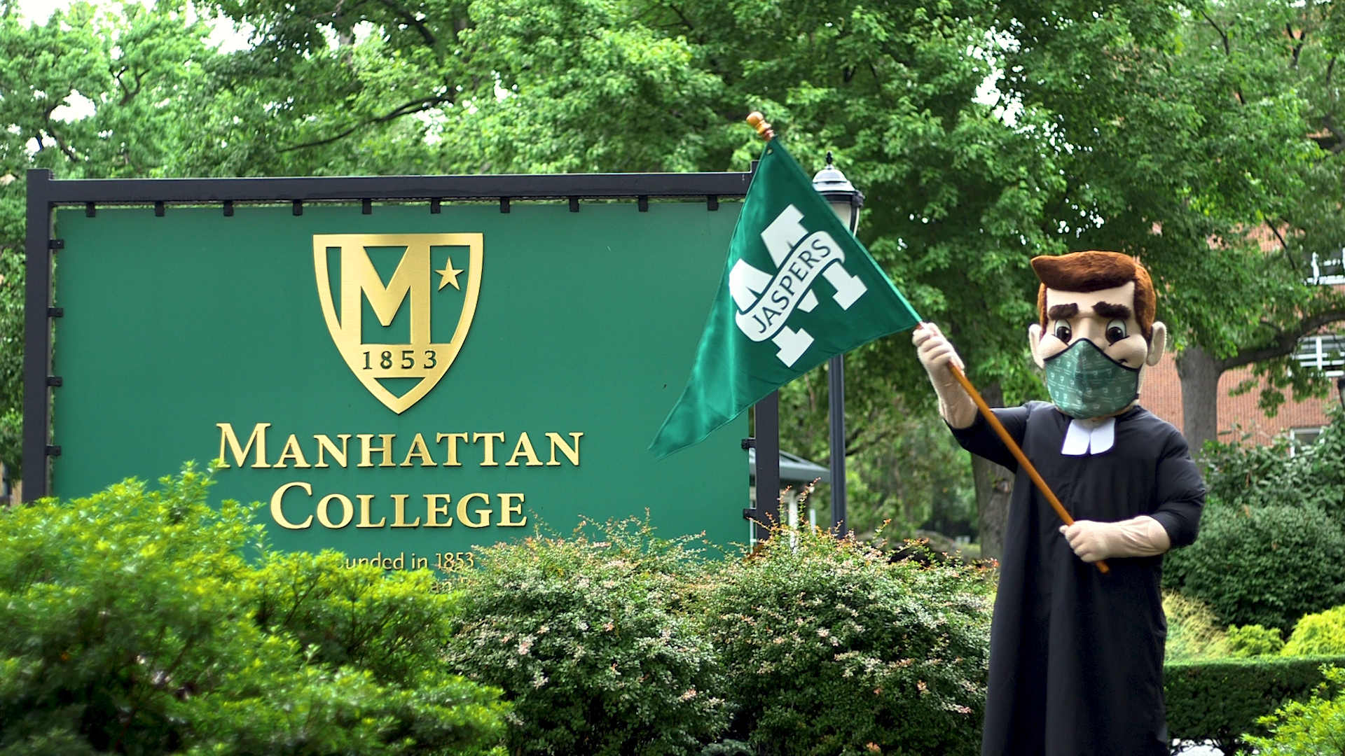 Photograph of Brother Jasper mascot standing in front of Manhattan College main entrance sign with a mask on.