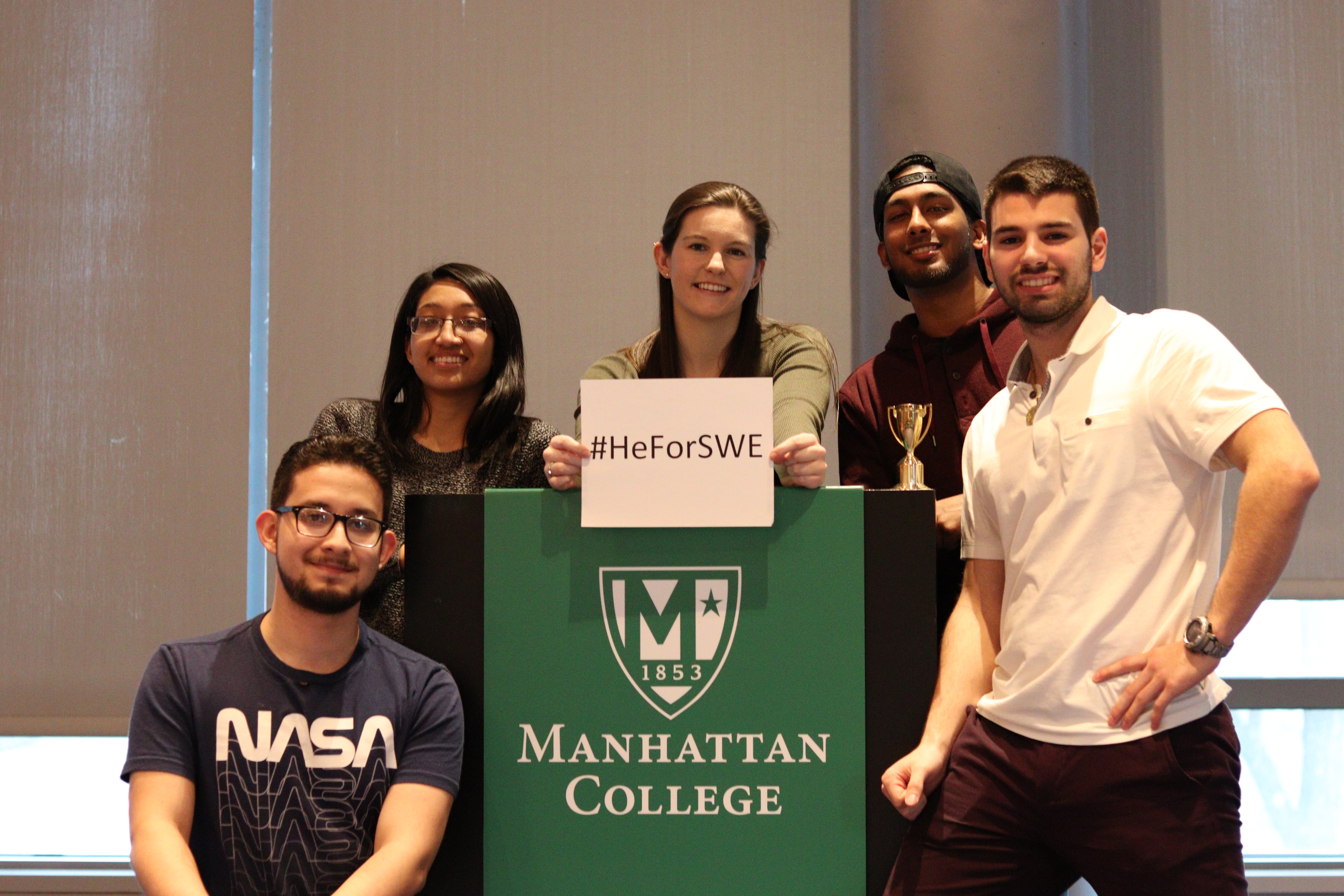 Five students standing by podium with trophy and sign that reads; hashtag (HeForSWE)