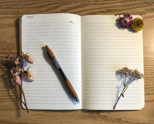 notebook surrounded with flowers