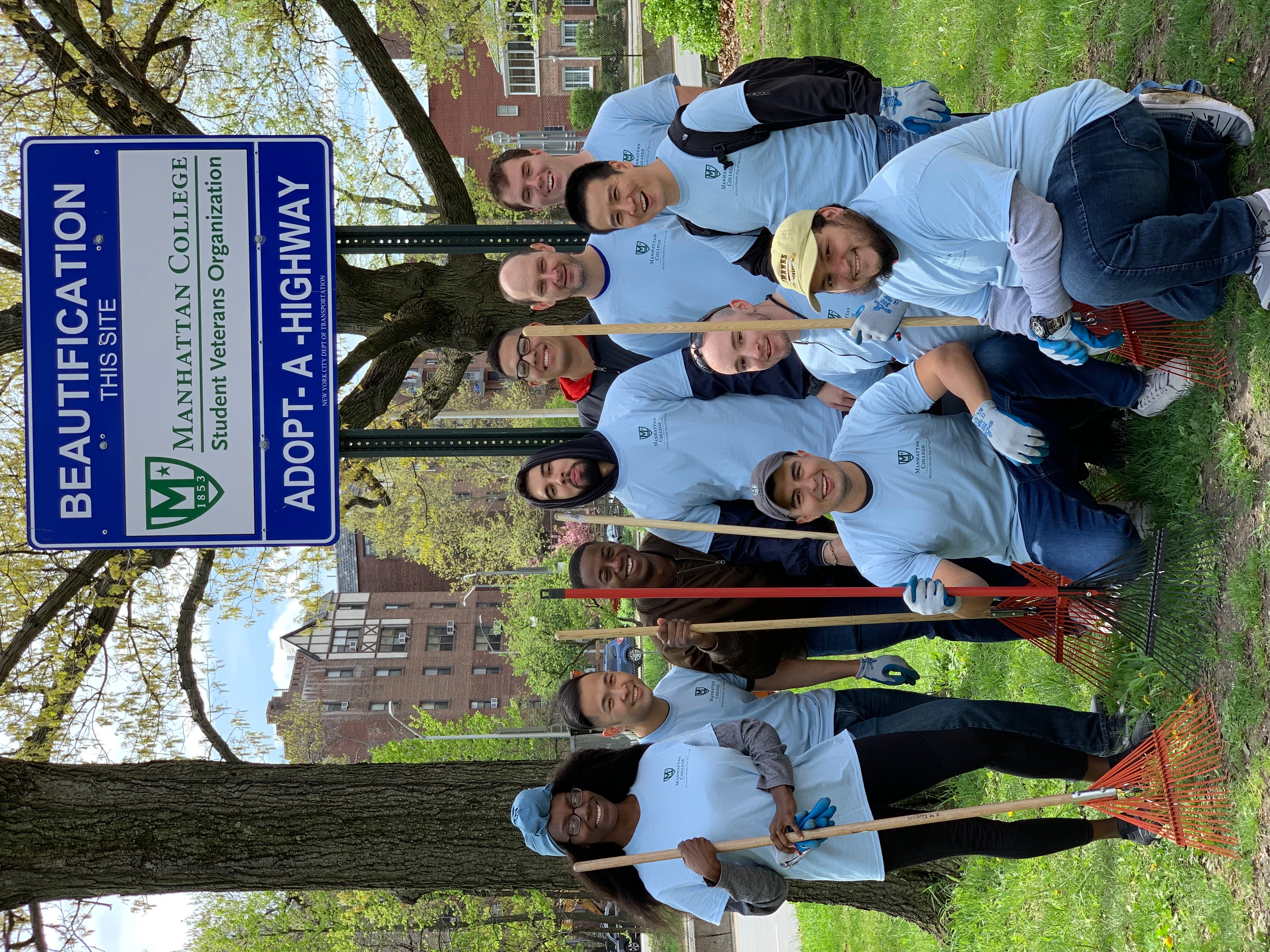 Veteran Students in front of adopt a highway sign with gardening tools.