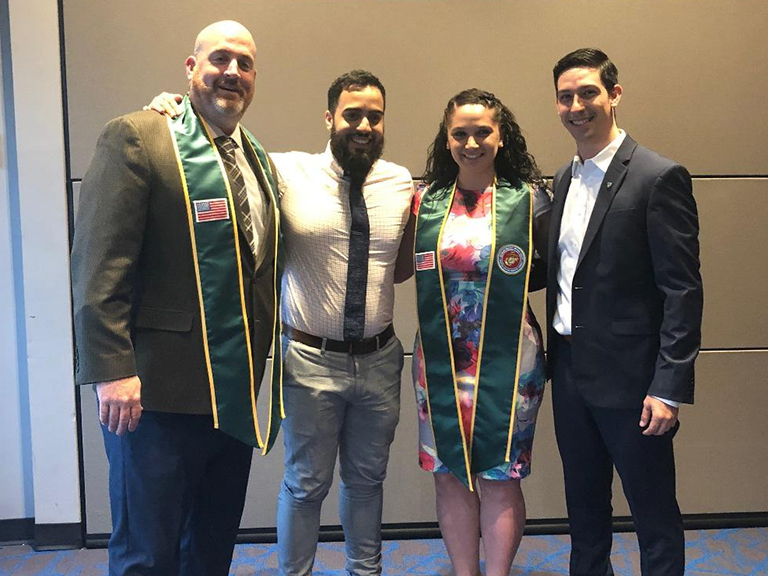 Four veteran students standing together wearing commencement stoles.